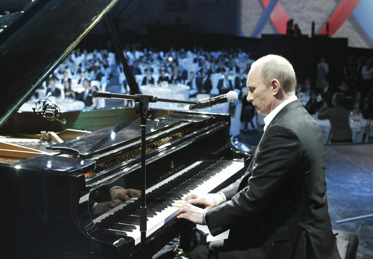 Russia's Prime Minister Vladimir Putin plays the piano at a char