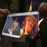 Iranske demonstranter afbrænder et billede af den amerikanske præsident foran USAs ambassade i Teheran.