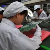 Arbejdere undersøger teknikken på Foxconn-fabrikken i Shenzen i Kina, hvor en stor del af Apples telefoner og iPad-computere produceres. Foto: Voishmel, AFP/Scanpix