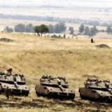 Israelske Merkava tanks holder nær grænsen til Syrien efter missilangrebene på iranske militære stillinger i Syrien natten til torsdag. / AFP PHOTO / MENAHEM KAHANA