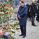 Sveriges statsminister Stefan Löfven ved blomsterbuketter foran Åhléns i det centrale Stockholm lørdag.