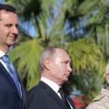Ruslands præsident Vladimir Putin står side om side med Syriens præsident Bashar al-Assad ved en militærparade i Latakia i syrien den 11. december. Under sit besøg erklærede Putin sejr over Islamisk Stat og meddelte, at nogle af de russiske soldater i Syrien nu vil blive kaldt hjem. . / AFP PHOTO / POOL / Mikhail KLIMENTYEV