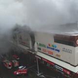 Russiske brandfolk kæmper for at få bugt med flammerne i et indkøbscenter i Sibirien søndag. Reuters/Handout