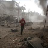 En frivillig fra det syriske Røde Halvmåne inspicerer et område i forstaden Ghouta, hvor raketter fra syriske kampfly har ramt. Foto: Samer Bouidani/DPA