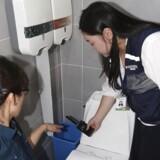 Kvindelige politibetjente undersøger et offentligt toilet for skjulte kameraer. Den slags er et stort problem i landet, men nu har politiet taget nye metoder i brug for at komme det til livs.