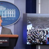 Press Secretary Sean Spicer delivers a statement while television screen show a picture of U.S. President Donald Trump's inauguration at the press briefing room of the White House in Washington U.S., January 21, 2017. REUTERS/Carlos Barria
