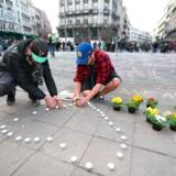 Folk lægger blomster og lys foran børsen i Bruxelles.