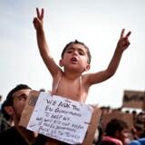 En syrisk dreng holdes op ved havnen i græske Chios. På skiltet står der: »Vi beder EUs regeringer hjælpe os. Vi dræber os selv, hvis EUs regeringer [sender] os tilbage til Tyrkiet.«