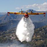 Flere hundrede brandmænd er udkommanderet i det sydlige Frankrig, hvor de kæmper med skovbrande, der er spredt sig ud over 900 hektar. Her ses et brandslukningsfly over Carros nær Nice i det sydlige Frankrig.