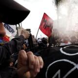 Brasiliansk politi må bruge pebberspray mod demonstranter 2. august, hvor tusinder protesterede mod legene, imens den olympiske ild blev båret gennem byen Niteroi/ AFP PHOTO / YASUYOSHI CHIBA