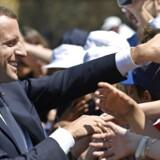 Frankrigs præsident Emmanuel Macron giver hånd til tilskuere i forbindelse med landets nationaldag. Exitpolls viser, at præsidentens parti, La République En Marche, står til et solidt flertal i underhuset ved søndagens parlamentsvalg.