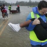 Frivillige redder tre børn fra deres oversvømmede hjem i James City i den amerikanske delstat North Carolina, hvor orkanen Florence ramte fredag. Chip Somodevilla/Ritzau Scanpix