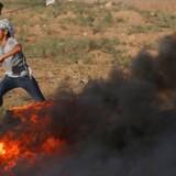 En palæstinensisk dreng kaster sten mod det israelske militær under en protest. Det er en protest mod Israels blokade af Gaza. Blokeringen betyder, at palæstinensere ikke kan vende hjem til deres hjemland over den israelske Gaza-grænse.