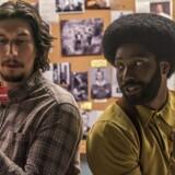 Adam Driver og John David Washington i rollerne som undercover-betjente med deres nyerhvervede medlemskort til Ku Klux Klan.