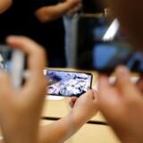 Selv om det er slut med de lange køer foran Apple-butikkerne ved nylanceringerne, kan iPhone-telefonerne fortsat mønstre et købedygtigt publikum fra morgenstunden, når der er nye varer på hylderne. Her bliver de nye telefoner studeret i Apple-butikken i Shanghai i Kina. Arkivfoto: Aly Song, Reuters/Scanpix