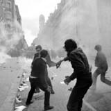 Man måtte leve for de penge og med den åndelige føde, man havde rede, for Paris' banker og biblioteker var lukket under de urolige dage i maj 1968. Her kaster studerende skyts mod politiet i Rue Saint-Jacques. Arkivfoto: AFP / Ritzau Scanpix
