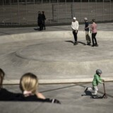 Legepladsen på Israels Plads i København. Piger ser på drenge, der skater og kører på løbehjul.