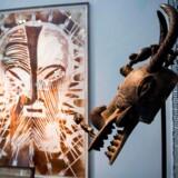 Frankrig kan nu se frem til en debat om tilbagelevering af afrikansk kunst. På billedet ses en gammel afrikansk maske og et moderne kunstværk, designet af den sydafrikanske kunstner Kendell Geers, på museet Carreau du Temple i Paris.