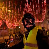 En maskeret »gul vest« på sin scooter nær Triumfbuen ved Champs-Élysées i Paris lørdag aften. Byens politikorps affyrede tåregas og vandkanoner under demonstrationen.
