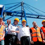 Den kinesiske shippinggigant Cosco overtog kontrollen med størstedelen af Piræus-havnen i Grækenland i 2016. På billedet ses Kinas premierminister, Li Keqiang (nummer fire fra venstre), sammen med den daværende græske statsminister, Antonis Samaras, under et besøg i Piræus i 2014. I de orange veste er græske havnearbejdere.