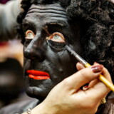 En make-up artist maler en mand sort i ansigtet. Han skal senere optræde som Sankt Nicolaus' hjælper Zwarte Piet. Arkivfoto: Jerry LampenEPA/Ritzau Scanpix