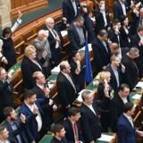 Politikere fra oppositionen viser deres identifikationskort frem og afsynger nationalsangen i det ungarske parlament under onsdagens samling. Protesten gælder premierminister Viktor Orbáns nyindførte forfatningsdomstole.