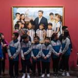 Flere kunstudstillinger er åbnet i Kina for at fejre 40-året for landets økonomiske reformer. Her ses skolebørn foran et maleri af Kinas leder Xi Jinping ved et udstlling i Hongkong.