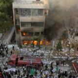 Bygningen, hvor også den svenske og den chilenske ambassade har til huse, stod i lys lue, da brandvæsenet nåede frem. Ophidsede demonstranter smadrede ambassaden, inden de satte ild til bygningen. Foto: Khaled al-Hariri/Reuters
