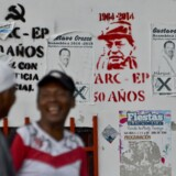 """Mænd ved siden af graffiti, som henviser til den tidligere Farc-leder Alfonso Cano og bevægelsens stifter, Pedro Antonio Marin """"Tirofijo"""". Aftalen bringer en af verdens længst varende konflikter til en afslutning. """"Aldrig igen skal forældre begrave deres sønner og døtre, fordi de er dræbt i krigen,"""" siger den nuværende Farc-leder, Rodrigo Londono. Scanpix/Luis Robayo"""