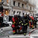 Redningsfolk hjælper en såret person væk fra stedet, hvor der lørdag har været en eksplosion i Paris.