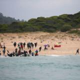 En gruppe migranter gør landgang blandt badegæster på Cañuelo-stranden nær den sydspanske by Tarifa i juli sidste år, hvor den illegale trafik over Gibraltarstrædet satte ny rekord.