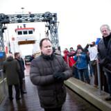 Dansk Folkepartis Martin Henriksen står ved færgelejet til Lindholm, mens lokale viser deres modstand mod planerne om at omdanne øen til center for udviste asylansøgere.