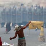 Demonstranter kaster sten mod en række medlemmer af Venezuelas Nationalgarde i Pacaraima ved grænsen til Brasilien.
