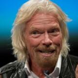 Richard Branson i sit es med stort smil og vinderfingrene i vejret, her under en tale på National Air and Space Museum i Washington i februar i år. Rummet optager ham meget – også i højere luftlag, end hans flyselskab kommer.