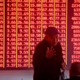 I Kina symboliserer røde aktiekurser, at markedet er steget - i modsætning til resten af verden. Det er fordi, rød betyder glæde og held i Kina. Foto: STR/AFP/Ritzau Scanpix