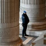 En politimand står udenfor Palais de Justice i Bruxelles, hvor Mehdi Nemmouche torsdag aften fik sin dom. Den 33-årige franskmanden, der har fået kamptræning fra Islamisk Stat i Syrien, er hovedmistænkt i et skudattentat på Det Jødiske Museum i Bruxelles for snart fem år siden. Fire personer blev dræbt under attentatet. Foto: JOHN THYS / AFP