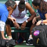Serena Williams bliver tilset af en læge, efter hun søndag måtte trække sig i tredje runde af WTA-turneringen i Indian Wells. Jayne Kamin-Oncea/Ritzau Scanpix