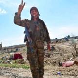 En soldat fra den kurdisk-ledede milits Syriens Demokratiske Styrker (SDF) giver V-tegnet efter sejren over IS' sidste bastion i det østlige Syrien. Men selvom Islamisk Stat ikke længere har noget fysisk territorium, er der flere gode grunde til ikke at glæde sig for tidligt.