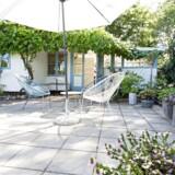 Foran kolonihavehuset er der anlagt en stor terrasse. Langs huset vokser opstammede vindruer. Acapulco-stolene er selvfølgelig blå og hvide.