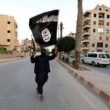 Et soldat fra Islamisk Stat vifter med den sorte fane i Raqqa, juni 2014. På det tidspunkt var byen terrorbevægelsens de facto hovedstad og gerningssted for krigsforbrydelser. Danske Jacob El-Ali var i byen, da terrorbevægelsen henrettede dusinvis af krigsfanger og stillede deres afhuggede hoveder til skue på torvet.
