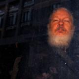 Julian Assange efter sin anholdelse uden for Ecuadors ambassade og på vej væk i et salatfad.