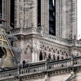 Konstruktionsarbejdere installerer kæmpemæssige presenninger henover taget på Notre Dame i Paris.
