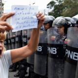 En kvinde deltager i en demonstration uden for den venezuelanske flådes hovedkvarter i hovedstaden Caracas lørdag. På hendes skilt står: Ven: du som forsvarer en korrupt regering, følg forfatningen. Juan Barreto/Ritzau Scanpix