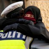 Ayah i niqab trøstes af en polititjenestemand, der efter ti måneders efterforskning nu er renset for anklager om, at hun havde handlet forkert ved at give kvinden et kram. Billedet er taget 1. august 2018 på Nørrebro i København – dén dag, forbuddet mod at bære niqab og skimaske – »tildækningsforbuddet«– trådte i kraft.