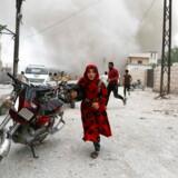 En syrisk pige løber for at søge dækning under et luftangreb i Idlib, torsdag. Det syriske regime og de russiske allierede har de seneste seks uger eskaleret bombardementerne i landets sidste oprørskontrollerede provins.