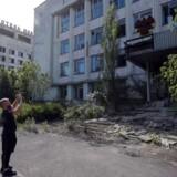 En turist tager billeder af en forladt bygning i spøgelsesbyen Pripjat, tæt ved Tjernobyl, foråret 2019.