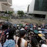 Demonstranter bliver mødt af kampklædte betjente efter at have blokeret centrale veje omkring regeringshovedkvarteret i Hongkong.
