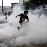 Tåregassen hang onsdag lavt over Hongkong, hvor en af demonstranterne forsøgte at slippe væk.