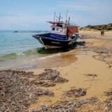 Et »spøgelsesskib« efterladt på stranden nær byen Ribera i den sicilianske Agricento-provins. Selvom relativt få migranter når helt frem til de italienske kyster, har mange blandt dem lyssky ærinder.
