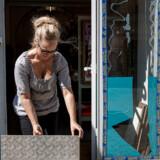Susanne Lindberg er i gang med at rydde op efter at store udstillingsvinduer til hendes trykkeri i Malmøs centrum blev blæst ind ved en eksplosion rettet mod en natklub på den anden side af gaden.